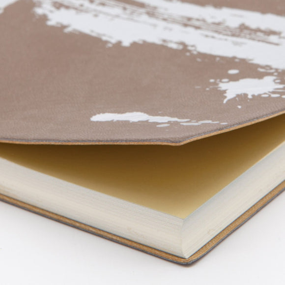 A notebook featuring a brown cover and lustrous silver paintstroke effect on the cover. The edges of the pages are printed with a similar effect.