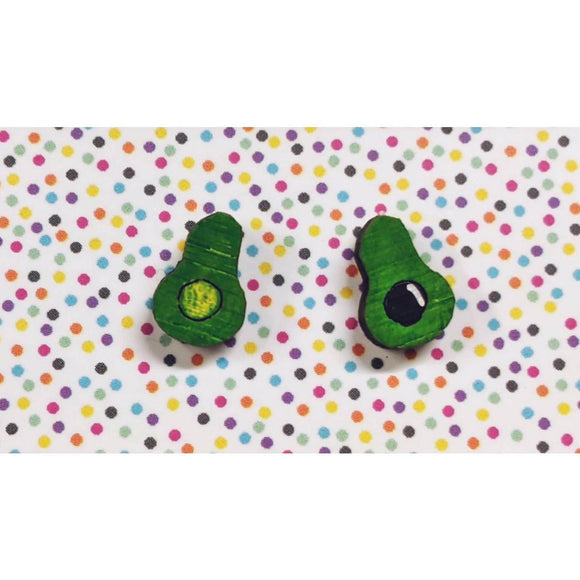 A pair of intricately hand coloured studs depicting two halves of an avocado that has been cut open. One side has the avocado stone present.