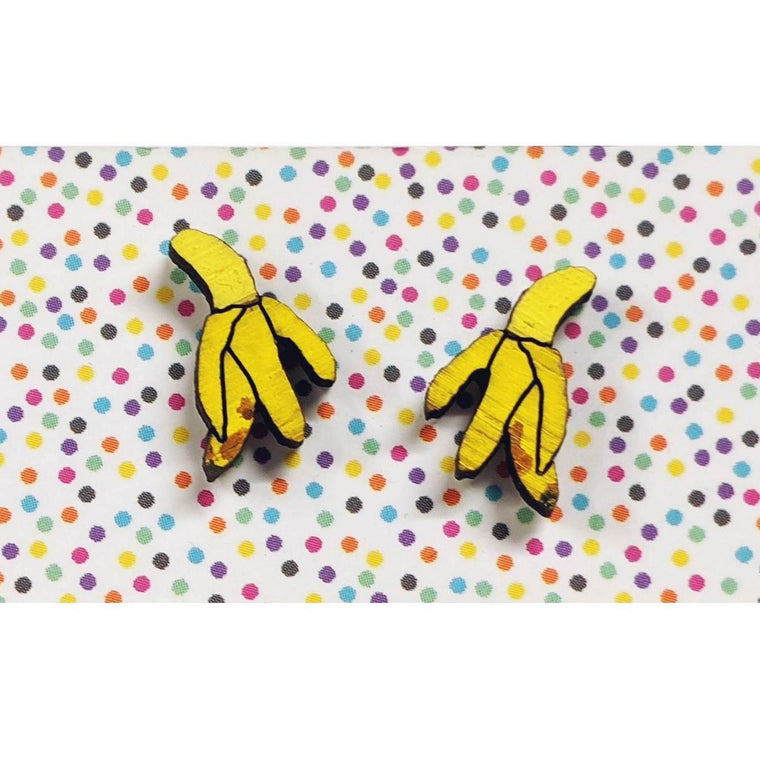 A pair of intricately hand coloured studs depicting bananas that have been half peeled. The peeled layers hang down. Displayed on a rainbow polka dot background.