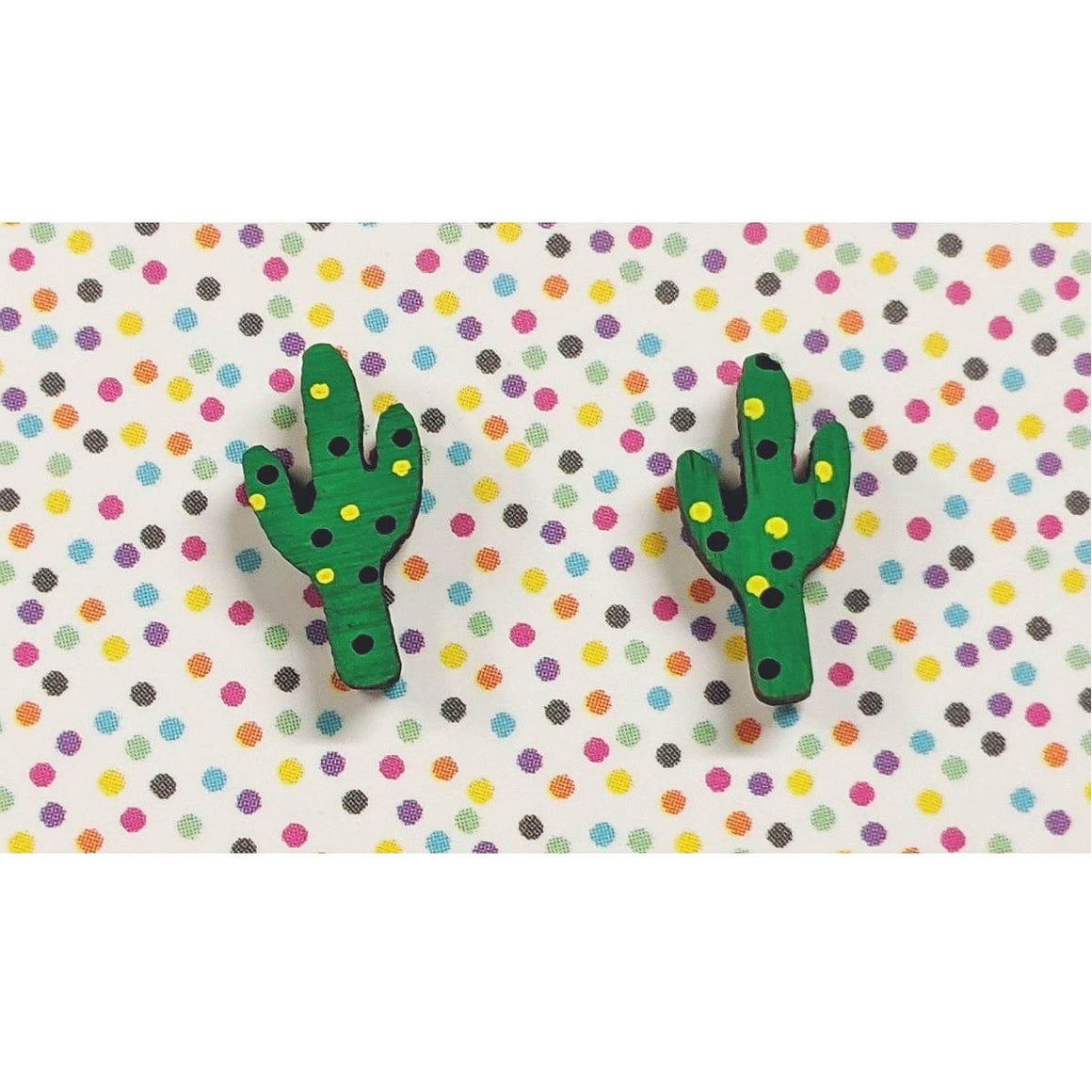 A pair of intricately hand coloured studs depicting green cactuses with black and yellow dots.