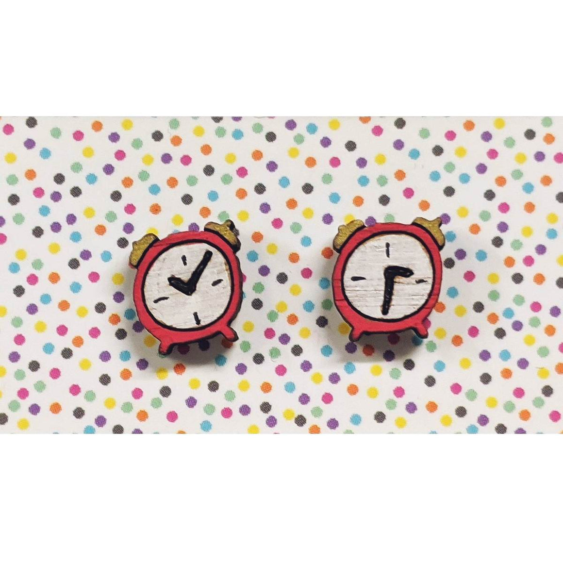 A pair of intricately hand coloured studs depicting two retro red analog alarm clocks with vintage style bells on top. They show different times.