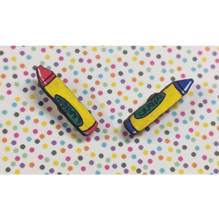A pair of intricately hand coloured studs depicting two individual crayons. The colours crayons vary, but they all have a a yellow and green label with the word CRAYON written on them.