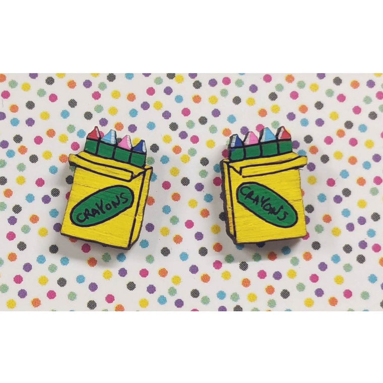 A pair of intricately hand coloured studs depicting packs of rainbow crayons. The packs are yellow with the word crayon written on them. Shown on a rainbow polka dot background.