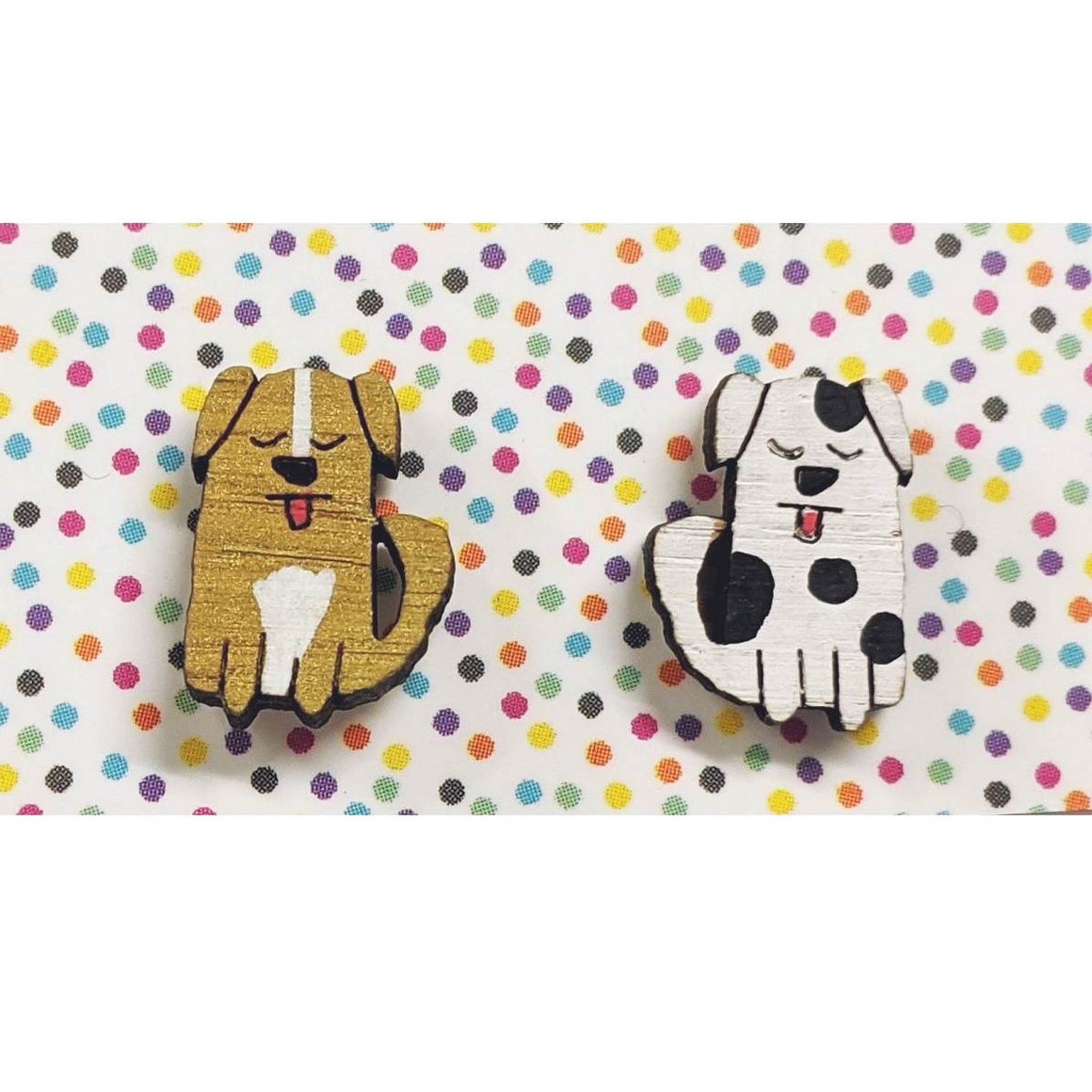 A pair of intricately hand coloured studs depicting dogs with their tongues out as if panting. The colours of the dogs vary, this pair are brown and white, and white and black