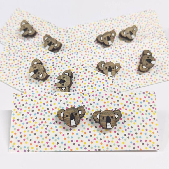 A pair of intricately hand coloured studs depicting koala heads, in grey and white. Displayed on a rainbow polka dot background.