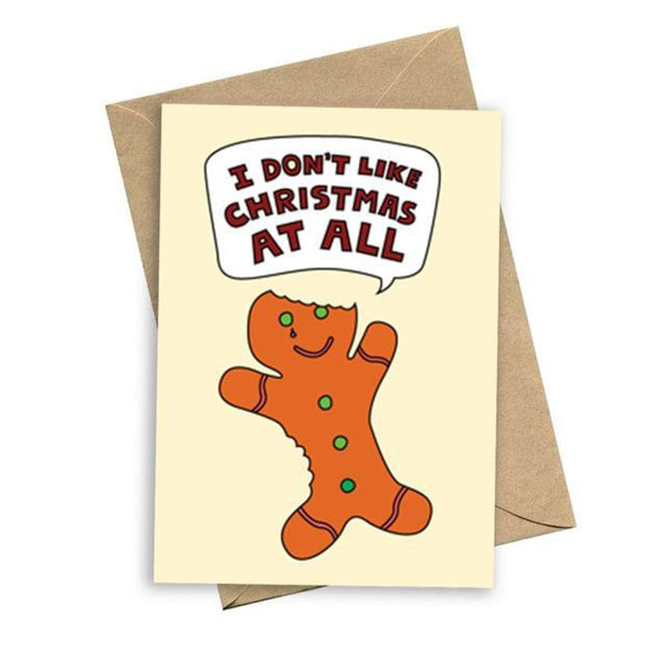 Image featuring a card with bold text saying I don't like christmas at all with a graphic illustration of a bitten ginger bread man with green buttons