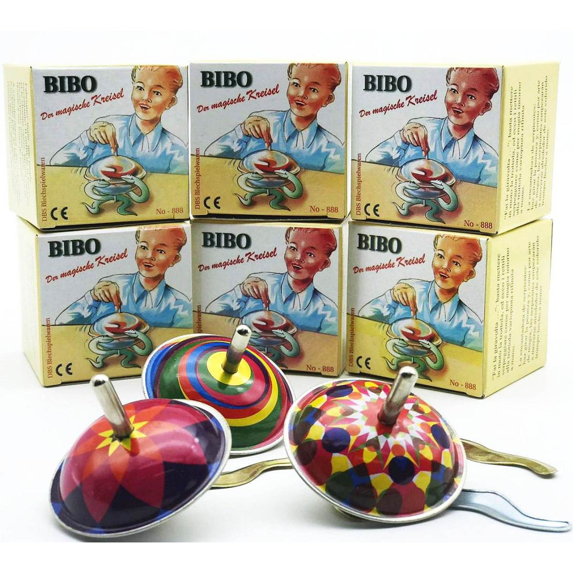 "Three brightly coloued tin spinning tops, pictured in front of a pile of boxes. The boxes feature the text "" Bibo Der Mahische Kreisel"" and an illustration of a child playing with a spinning top. There a metal snake shape pieces scattered around the spinning tops."