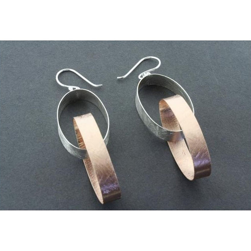 A pair sterling silver and rose gold plated two hooped drop earrings sitting on top of a grey background