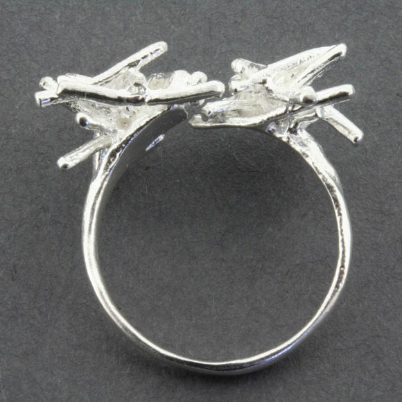 A Silver Ring, featuring a silver formation of kindling like sticks also made of silver.