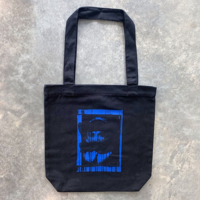A black tote bag featuring a detail of a artwork by Lindy Lee in deep electric blue.