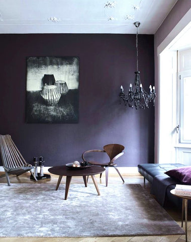 Dark and moody living interior with ultra violet walls