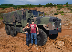 Kathy & Kevin Coleman In Front Of Military Vehicle Used For Tours