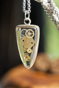 This time-less Steampunk necklace features a clear vitreous arrowhead pendant filled with one-of-a-kind watch parts.