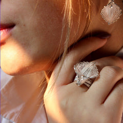 A model closeup that wears a filigree jewellery set of earrings and ring