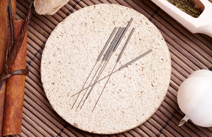 Acupuncture-needles-laying-on-the-stone-mat-with-cinnamon-garlic-and-herbs-around