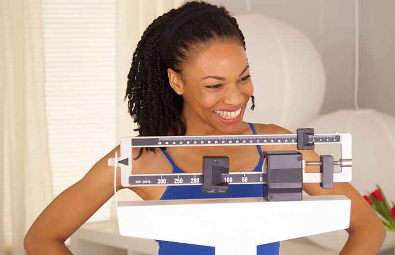 African-woman--sitting-on-a-weight-scale-feeling-happy-and-proud-of-herself