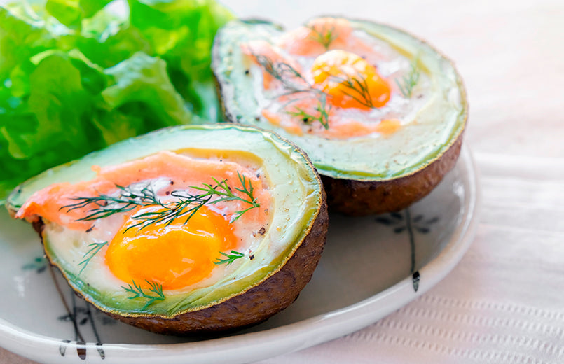 Avocado-with-egg-on-a-plate-with-salad-in-the-background