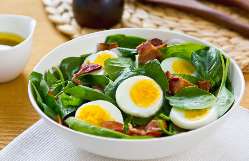 Bacon-with-boiled-egg-and-spinach-salad-in-a-white-bowl