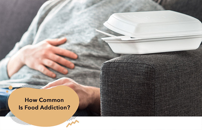 man-on-couch-with-hand-on-belly-and-take-out-box