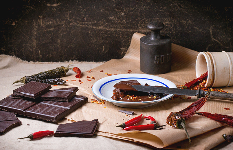 Chocolate-block-melted-chocolate-on-a-plate-and-red-chilli-peppers-on-wooden-table