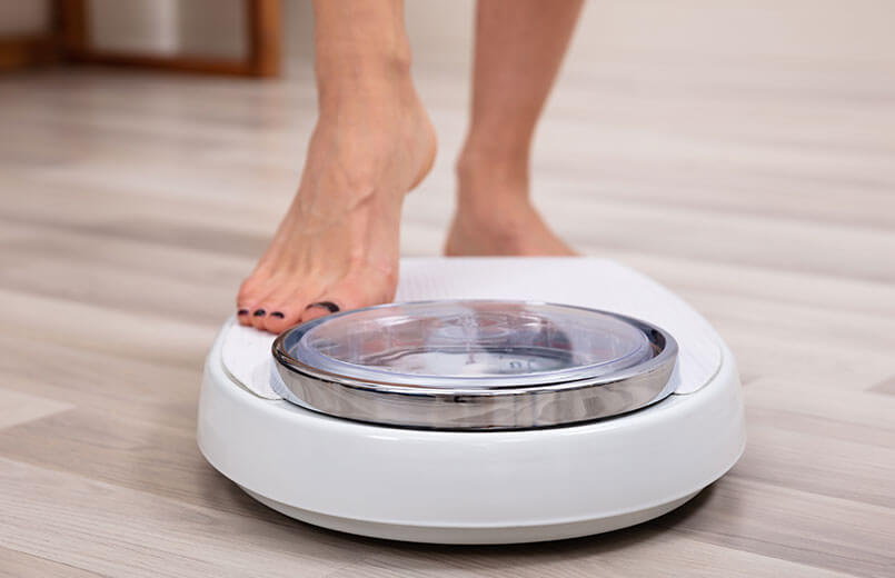 Close-up-Of-A-Human-Foot-Stepping-On-Weighing-Scale-Over-Hardwood-Floor