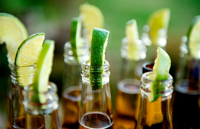 Close-up-image-of-multiple-beer-bottles-with-limes-inserted