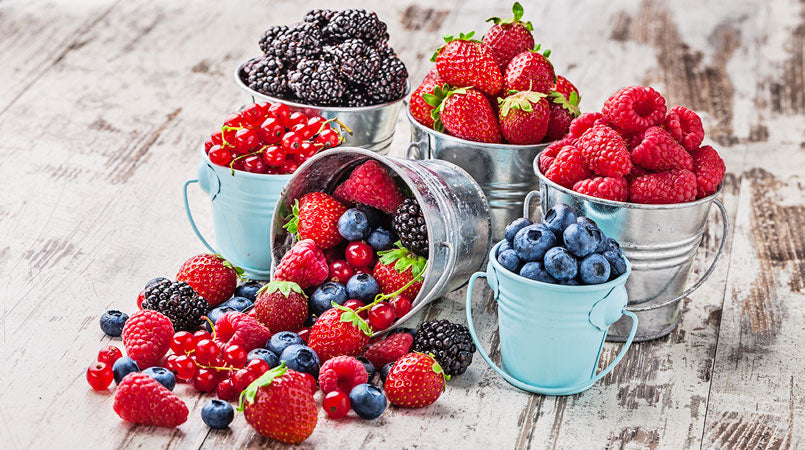 colorful-fresh-berries-arranged-in-metallic-cans-on-rustic-white-wooden-table-with-fruits-spilled-on-the-table