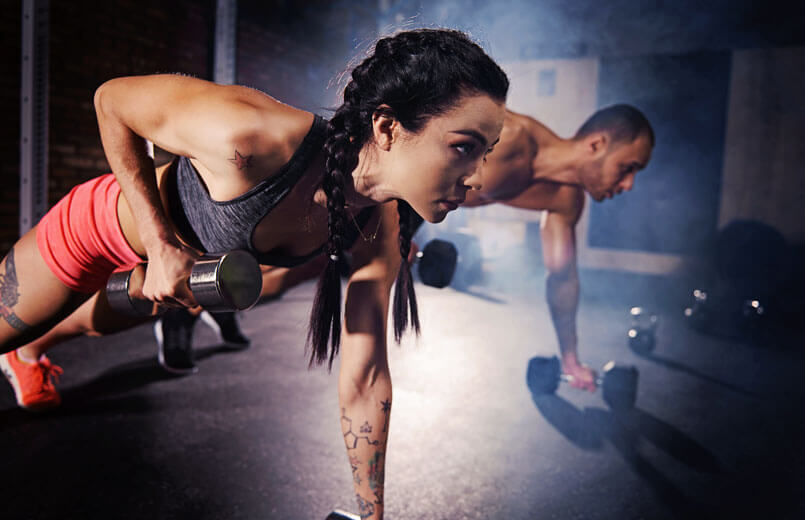 Confident-couple-working-out-with-dumbbell