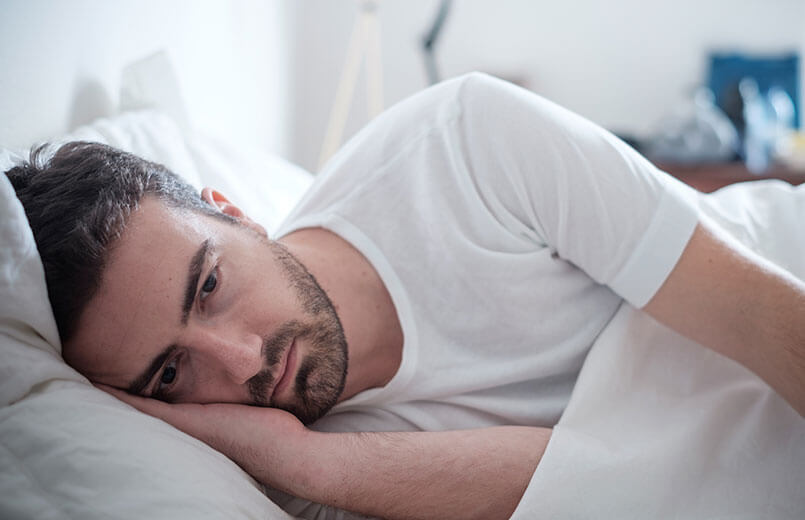 Depressed-man-lying-in-his-bed