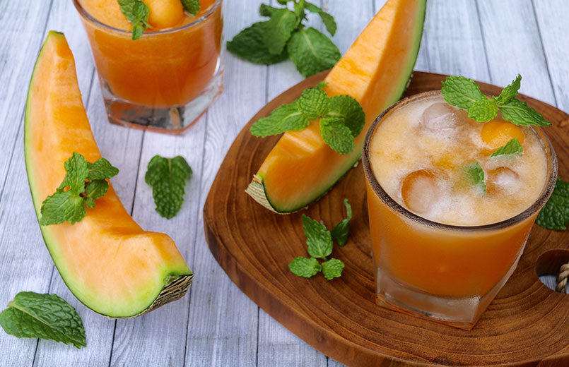 Fresh-cantaloupe-juice-served-in-a-glass-with-ice-cubes-and-fresh-mint-leaves-with-cantaloupe-slices-and-wooden-background