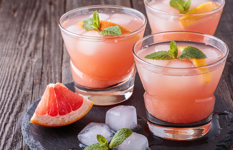 Grapefruit-juice-with-ice-and-mint-in-glasses-over-a-wooden-background