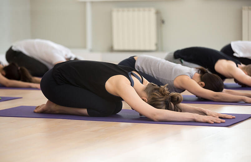 Group-of-people-in-Balasana-pose-in-a-gym