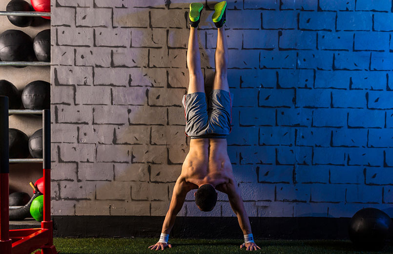 Handstand-push-up-man-workout-at-gym