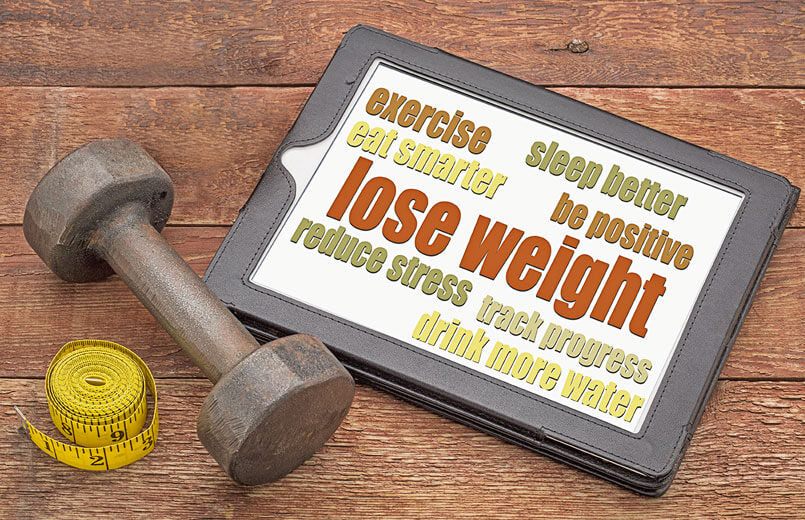 Losing-weight-tips-on-a-digital-tablet-with-a-dumbbell-and-tape-measure