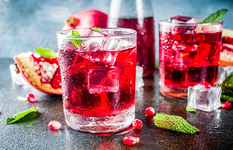 Pomegranate-drink-with-sparkling-water-ice-cubes-over-a-dark-blue-grey-background