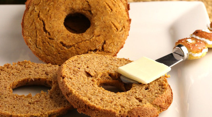 Pumpkin-Bagels-on-a-white-plate-with-butter-on-knife-and-pumpkin-in-the-background
