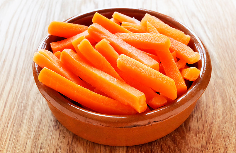 Raw-carrot-sticks-in-brown-rustic-bowl-on-wooden-table
