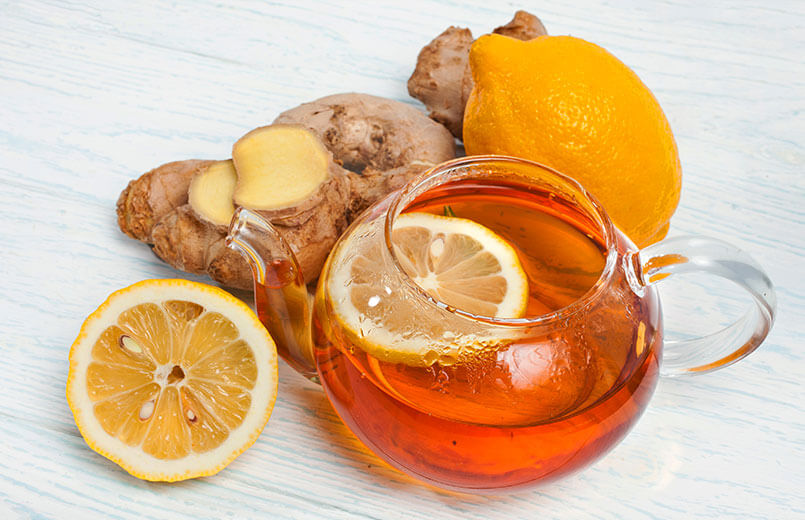 Tea-in-teapot-with-ginger-roots-and-lemon-slices-on-white-wooden-background