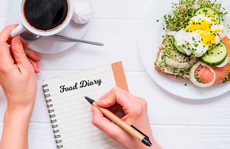 Woman-taking-breakfast-and-writing-in-notebook