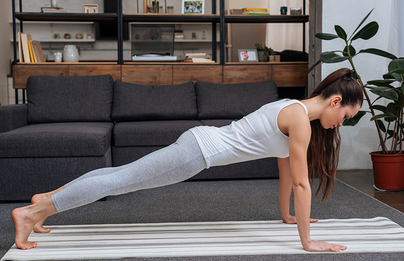 Young-Woman-Practicing-Plank-Pose--at-Home