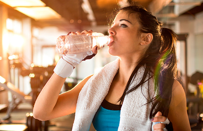 Young-athletic-woman-drinking-water-in-gym