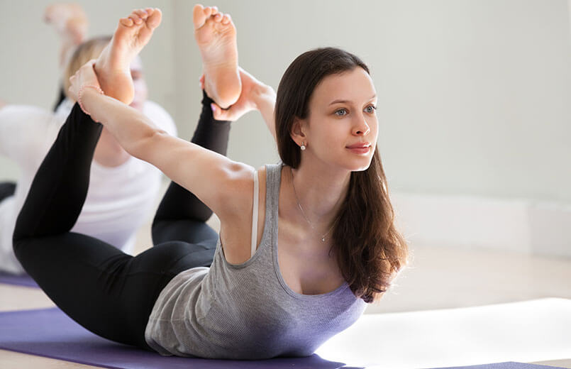 Young-sporty-attractive-woman-practicing-yoga-doing-Dhanurasana