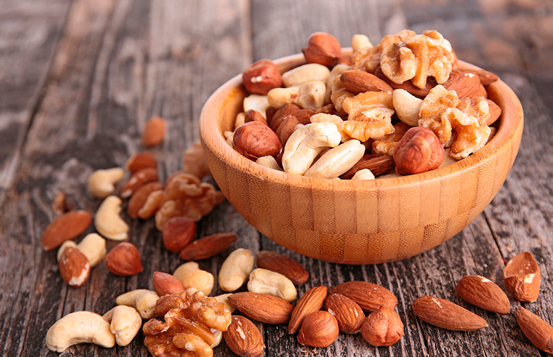assotments-of-nuts-in-a-wood-bowl-on-wooden-background