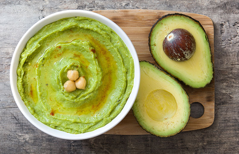 avocado-hummus-in-bowl-on-wooden-table-top-view