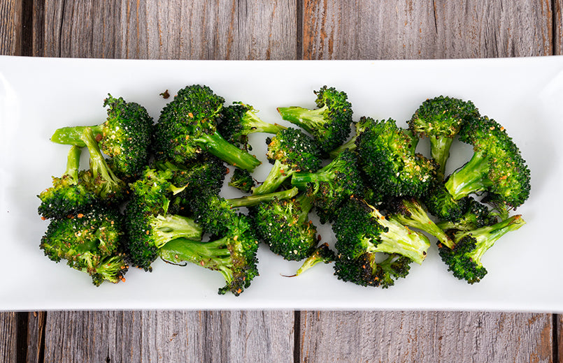 baked-roasted-broccoli-on-a-white-plate-on-wooden-table