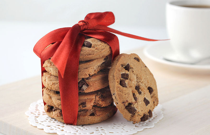 batch-of-chocolate-chips-cookies-wrapped-with-red-ribbon-on-a-white-table