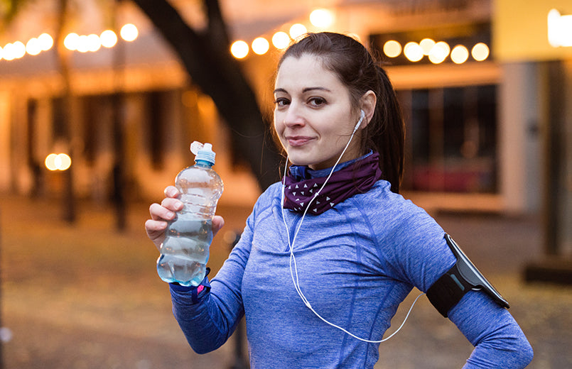 beautiful-young-woman-with-smart-phone-and-earphones-listening-music-resting-drinking-water-from-bottle