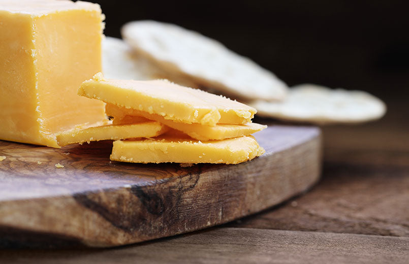 block-of-cheddar-cheese-and-slices-over-a-rustic-background