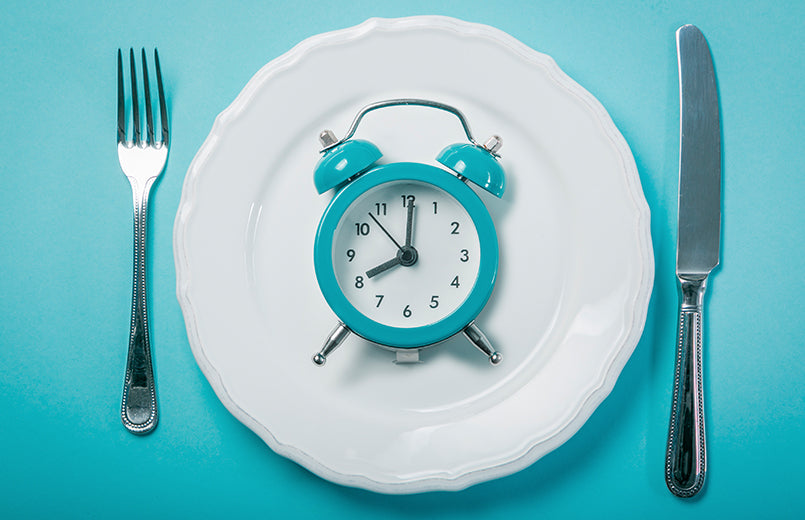 blue-clock-on-a-white-plate-fork-and-knife-on-blue-background-intermittent-fasting-concept