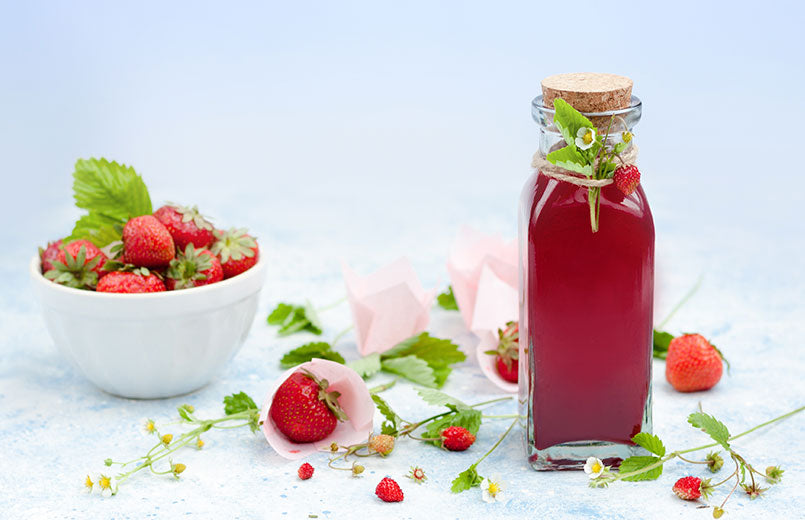bottle-of-homemade-strawberry-syrup-with-wild-strawberry-and-strawberry-fruit-in-a-white-bowl-on-light-background